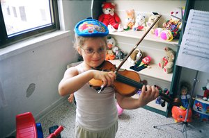At age of four playing with toys  and the violin